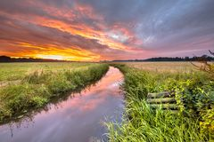 Warm indian summer sunrise over lowland river. Grootdiep near Oosterwolde, Friesland, Netherlands Stock Photo