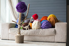 Warm interior with merino wool balls in multicolour on white sof Stock Images