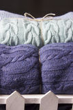 Warm knitted blankets folded stack. Comfort and convenience. Warm knitted blankets folded stack. Plaid mint color over blue homemade quilts, hand-knitted. The Stock Photo