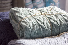 Warm knitted blankets folded stack. Comfort and convenience. Warm knitted blankets folded stack. Plaid mint color over blue homemade quilts, hand-knitted. The Royalty Free Stock Photo
