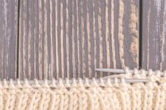 Warm knitted pattern of woolen yarn with needles. Warm knitted pattern of woolen yarn on gray rustic wooden background. Beggining of new handmade knitted scarf stock photography
