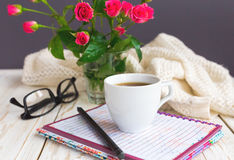 Warm knitted plaid, glasses, coffee, notebook and pensil Stock Photos