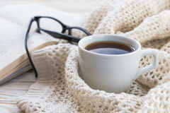 Warm knitted plaid, glasses, cup of hot coffee and book Stock Photo