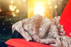 warm knitted scarf on chair, christmas tree and burning fireplac Stock Image