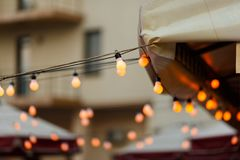 Warm light bulbs at the evening event. String wired with warming Light Bulbs hanging in the area of wedding events celebration in the night royalty free stock image