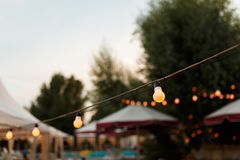 Warm light bulbs at the evening event. String wired with warming Light Bulbs hanging in the area of wedding events celebration in the night stock image
