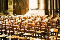 Neatly arranged chairs for service in a catholic church. Warm light in the church illuminates the places for the upcoming service royalty free stock photos
