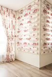 Warm light through sheer white tulle and vintage floral curtains, blinds with red roses in the bedroom. Interior design Royalty Free Stock Images
