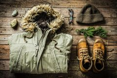 Winter warm male clothes -  jacket, boots, warm hat. Warm male clothes warm jacket, boots and hat. Winter or christmas weekend in country cottage cabin concept Royalty Free Stock Image