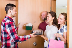 Warm meeting of friends. Holding gifts and sweets Stock Photo