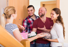 Warm meeting of happy friends. Holding gifts and sweets Stock Image