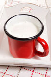 Warm milk in a red enamel mug. On a wooden serving tray Stock Photography