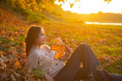 Warm moments of autumn. Woman pretty girl enjoy autumn. Girl relaxed lay fallen leaves on sunny autumn day. Warmth and. Coziness. Female autumn leaves stock image