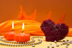 Warm, orange background with candles and heart Royalty Free Stock Photo