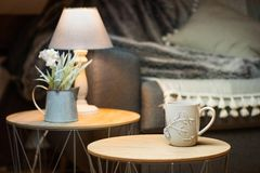 Team mug infusing in cosy warm room. In a warm, out of focus cosy living room, with lights, winter flowers and comfy blanket on a couch, a grey tea cup on a side royalty free stock image