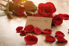 Warm photo of three red roses with petals on wood table and paper card for valentines day Royalty Free Stock Photography