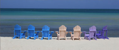 Warm place. Chairs for tourists at Palm beach, Aruba island, Caribbean Sea stock images