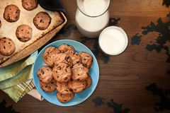 Warm plate of chocolate chip cookies and milk. Overhead view of plate and cookie sheet of chocolate chip cookies warm from the oven with glass of milk on vintage Stock Photo