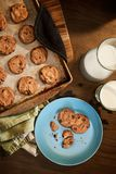 Warm plate of chocolate chip cookies and milk. Overhead view of plate and cookie sheet of chocolate chip cookies warm from the oven with glass of milk on vintage Royalty Free Stock Images