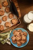 Warm plate of chocolate chip cookies and milk. Overhead view of plate and cookie sheet of chocolate chip cookies warm from the oven with glass of milk on vintage Stock Photos