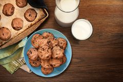 Warm plate of chocolate chip cookies and milk. Overhead view of plate and cookie sheet of chocolate chip cookies warm from the oven with glass of milk on vintage Stock Photography