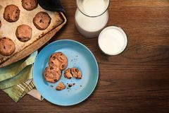 Warm plate of chocolate chip cookies and milk. Overhead view of plate and cookie sheet of chocolate chip cookies warm from the oven with glass of milk on vintage Stock Image