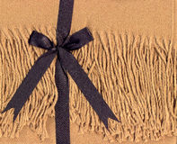 Warm Present. Sand coloured throw blanket tied with a black bow royalty free stock photos