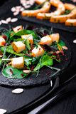 Warm pumpkin salad with mixed leaf of arugula, chard, in on black slate plate on black background. Grilled pumpkin. Close up. Royalty Free Stock Photo
