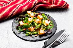 Warm pumpkin salad with mixed leaf of arugula, chard, in on black slate plate on grey background. Grilled pumpkin. Top view Royalty Free Stock Images