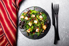 Warm pumpkin salad with mixed leaf of arugula, chard, in on black slate plate on grey background. Grilled pumpkin. Top view Stock Images