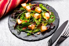 Warm pumpkin salad with mixed leaf of arugula, chard, in on black slate plate on grey background. Grilled pumpkin. Top view Royalty Free Stock Photography