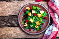 Warm pumpkin salad with raspberries and mixed leaf of arugula, chard, in brown plate on wooden rustic background. Top view. Warm pumpkin salad with raspberries Royalty Free Stock Photo