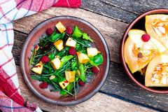 Warm pumpkin salad with raspberries and mixed leaf of arugula, chard, in brown plate on wooden rustic background. Top view. Warm pumpkin salad with raspberries Royalty Free Stock Image