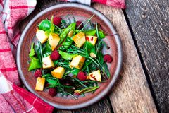 Warm pumpkin salad with raspberries and mixed leaf of arugula, chard, in brown plate on wooden rustic background. Top view. Stock Photo
