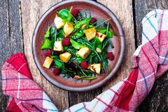 Warm pumpkin salad with raspberries and mixed leaf of arugula, chard, in brown plate on wooden rustic background. Top view. Stock Photos