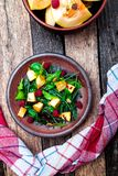 Warm pumpkin salad with raspberries and mixed leaf of arugula, chard, in brown plate on wooden rustic background. Top view. Royalty Free Stock Photography