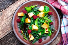 Warm pumpkin salad with raspberries and mixed leaf of arugula, chard, in brown plate on wooden rustic background. Top view. Royalty Free Stock Images