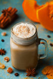 Warm pumpkin spiced latte or coffee in cup decorated cinnamon and anise on blue vintage background. Autumn, fall, winter hot drink Royalty Free Stock Photos