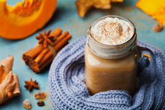 Warm pumpkin spiced latte or coffee in cup decorated knitted scarf on turquoise vintage background. Autumn, fall or winter drink. Royalty Free Stock Images