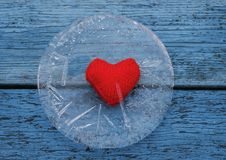 Warm red heart lies surrounded by the sharp cold of ice on a bl. The warm red heart lies surrounded by the sharp cold of ice on a blue table Royalty Free Stock Images