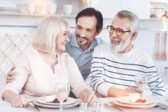 Cheerful adult son embracing his positive elderly parents. Warm relationships. Cheerful delighted aged couple sitting at the table while his adult son embracing Stock Images