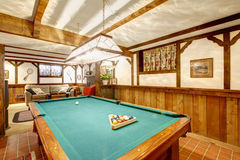 Warm rustic furnished living room with a fireplace and pool table. Cozy rustic designed living room with an entertainment area stock image