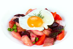 Warm salad. With fried egg, fish and vegetables royalty free stock image
