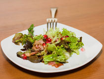Warm salad with bacon and pomegranate. And lettuce Stock Photo