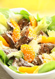 Warm salad with chicken liver. Lettuce, tangerine and sesame seeds Stock Photography