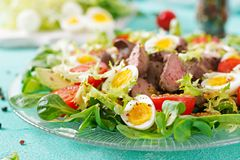 Warm salad from chicken liver, avocado, tomato and quail eggs. Healthy dinner. Dietary menu Royalty Free Stock Images