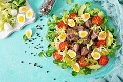 Warm salad from chicken liver, avocado, tomato and quail eggs. Healthy dinner. Dietary menu. Flat lay. Top view Royalty Free Stock Image