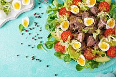 Warm salad from chicken liver, avocado, tomato and quail eggs. Healthy dinner. Dietary menu. Flat lay. Top view Stock Photos
