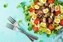 Warm salad from chicken liver, avocado, tomato and quail eggs. Healthy dinner. Dietary menu. Flat lay. Top view Stock Photography