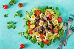 Warm salad from chicken liver, avocado, tomato and quail eggs. Healthy dinner. Dietary menu. Flat lay. Top view Stock Image